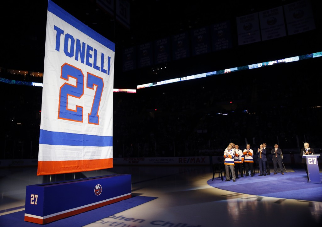 A banner with the name and number of former New York Islander Jon Tonelli is raised Friday, Feb. 21, 2020, in Uniondale, N.Y., as some of Tonelli's fo...