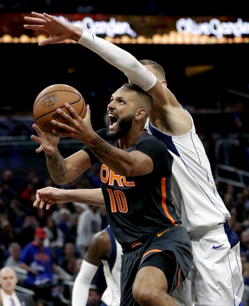 Orlando Magic guard Evan Fournier (10) is fouled by Dallas Mavericks forward Kristaps Porzingis while going up to shoot during the second half of an N...