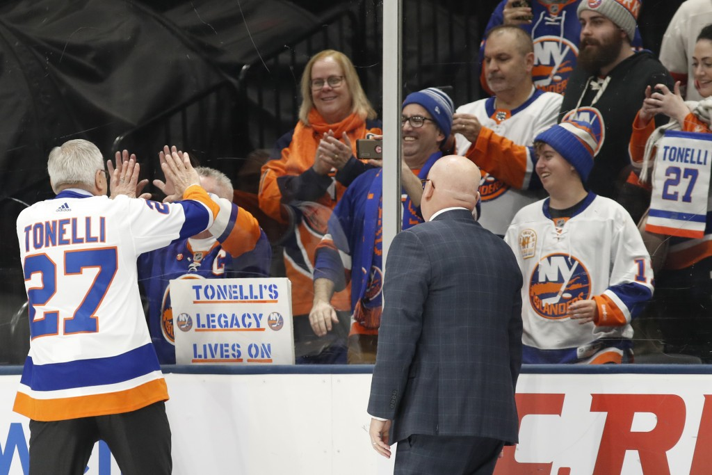 Former New York Islander John Tonelli, left, greets a fan on the other side of the glass as he leaves the ice following his jersey retirement ceremony...