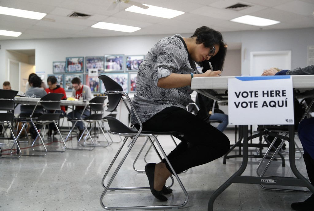 FILE - In this Feb. 15, 2020, file photo, a woman votes at an early voting location at the culinary workers union hall  in Las Vegas. Nevada Democrats...