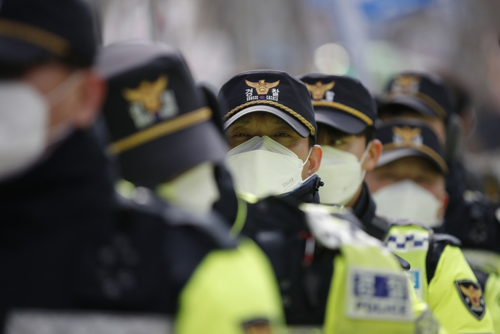Police officers wearing face masks stand guard during a rally in downtown Seoul, South Korea, Saturday, Feb. 22, 2020. South Korea on Saturday reporte...