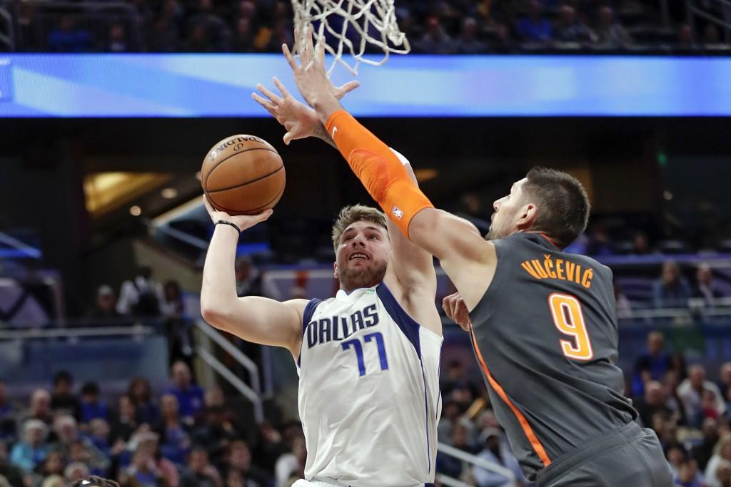 Dallas Mavericks guard Luka Doncic (77) shoots over Orlando Magic center Nikola Vucevic (9) during the first half of an NBA basketball game, Friday, F...