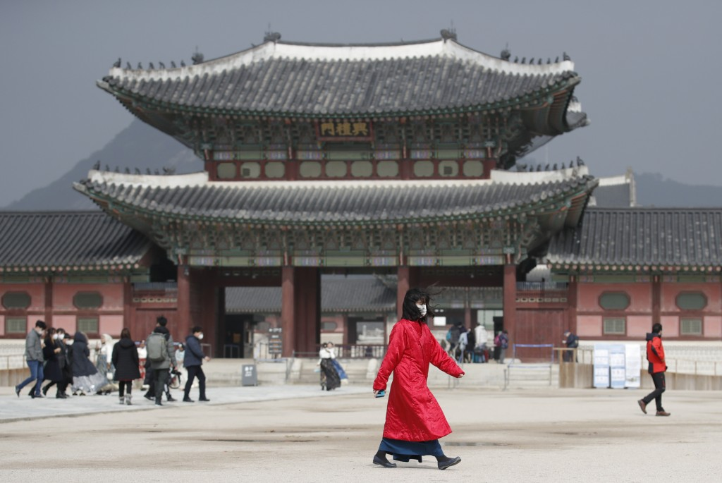 A woman wearing a face mask walks at the Gyeongbok Palace, one of South Korea's well-known landmarks, in Seoul, South Korea, Saturday, Feb. 22, 2020. ...