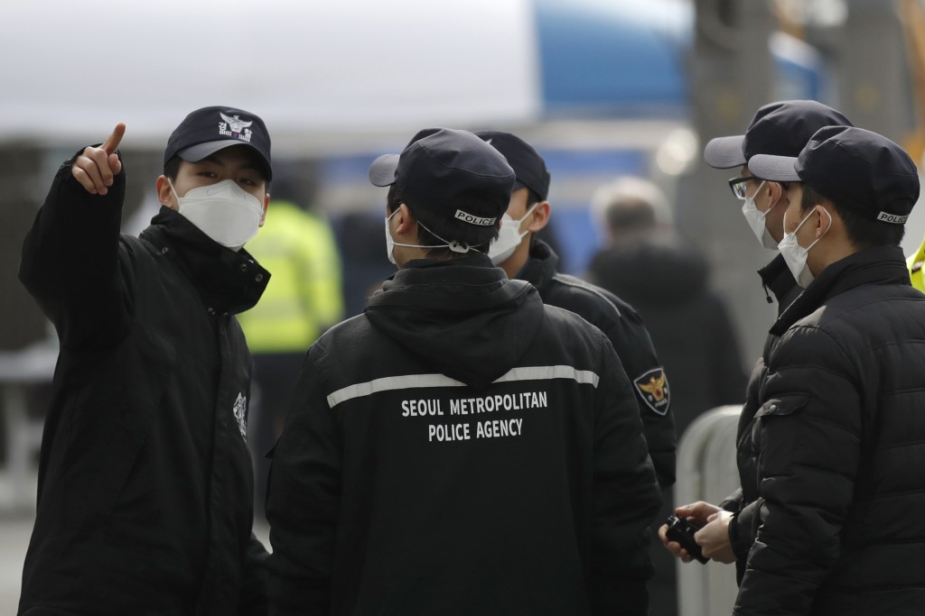 Police officers wearing face masks talk ahead of a rally in downtown Seoul, South Korea, Saturday, Feb. 22, 2020. South Korea on Saturday reported a s...