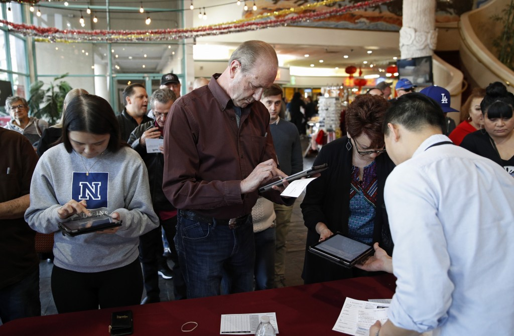 FILE - In this Feb. 15, 2020, file photo sign in on tablet computers at an early voting location in the Chinatown Plaza, in Las Vegas. Nevada Democrat...