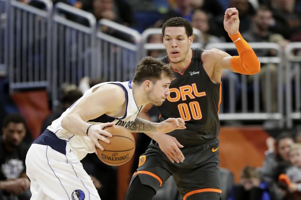 Dallas Mavericks guard Luka Doncic, left, drives around Orlando Magic forward Aaron Gordon (00) during the second half of an NBA basketball game, Frid...