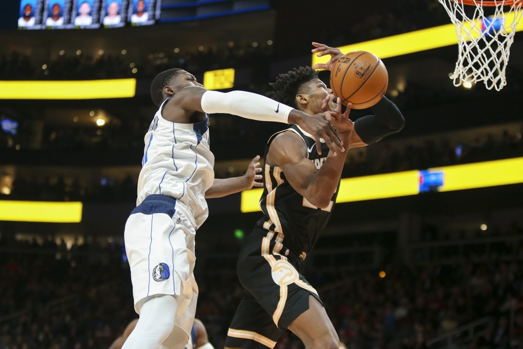 Dallas Mavericks forward Dorian Finney-Smith (10) fouls Atlanta Hawks guard Cam Reddish (22) in the first half of an NBA basketball game Saturday, Feb...