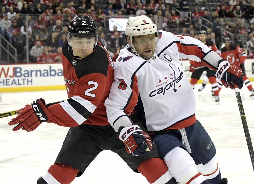 Washington Capitals left wing Alex Ovechkin (8) and New Jersey Devils defenseman Colton White (2) chase after the puck during the first period of an N...