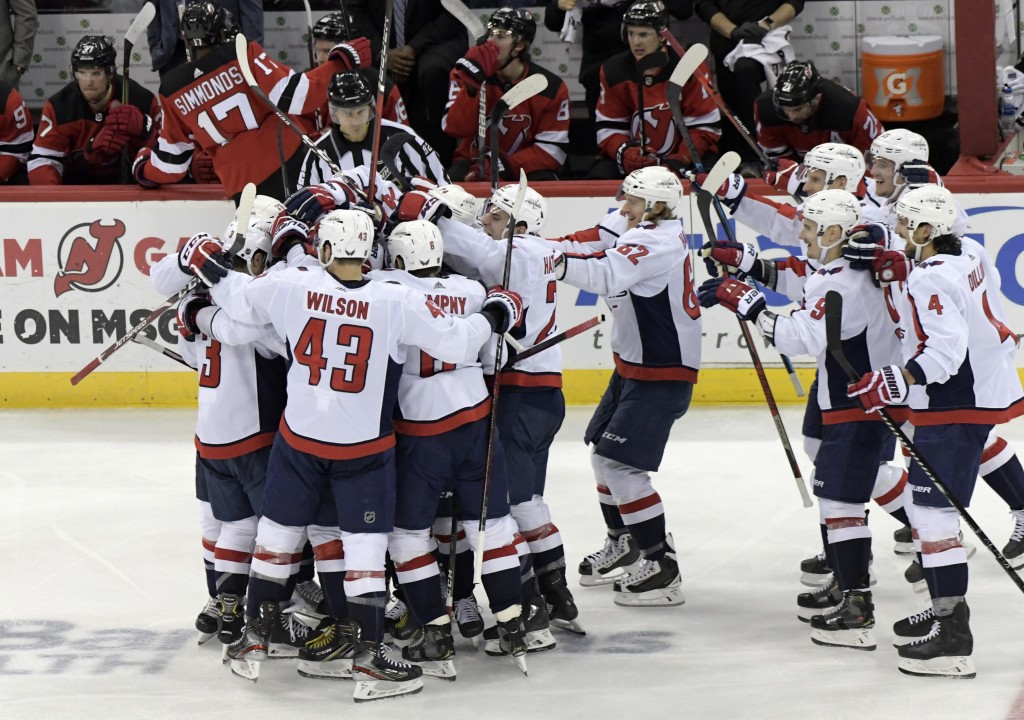 The Washington Capitals celebrate with Alex Ovechkin (8) after he scored his 700th career goal during the third period of an NHL hockey game against t...