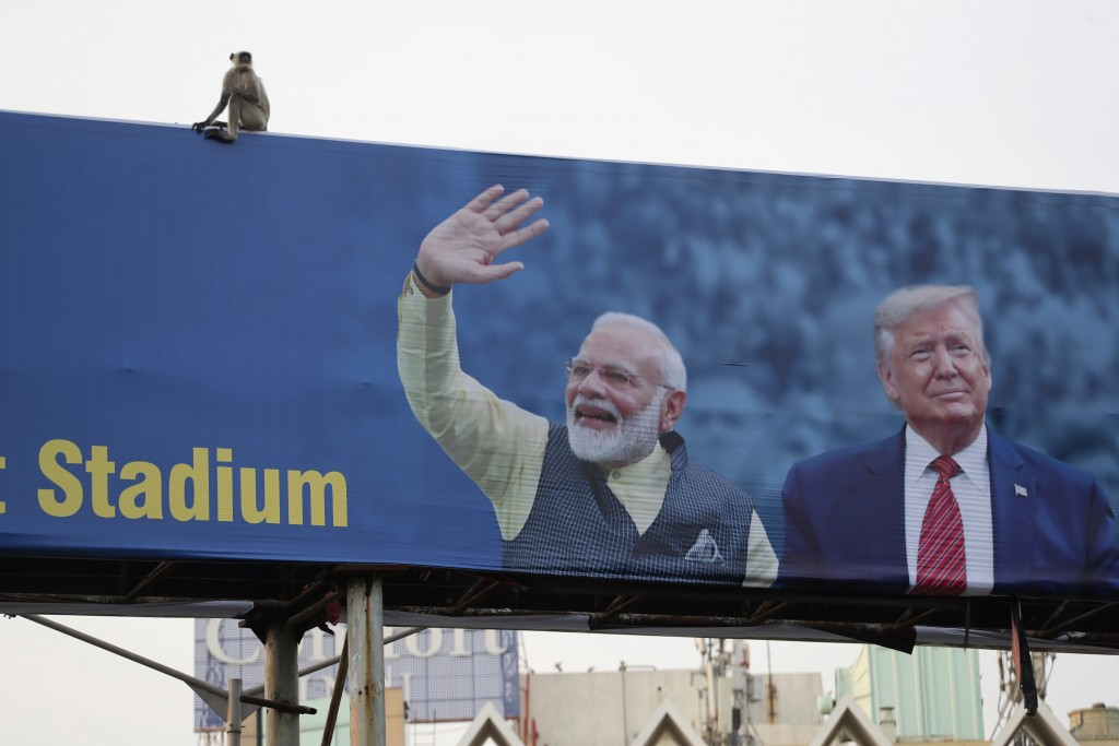 FILE- In this Feb. 19, 2020, file photo, a monkey sits on a hoarding showing India Prime Minister Narendra Modi and President Donald Trump welcoming T...
