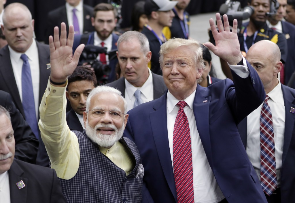 FILE - In this Sept. 22, 2019, file photo, India Prime Minister Narendra Modi and President Donald Trump walk the perimeter of the arena floor to gree...