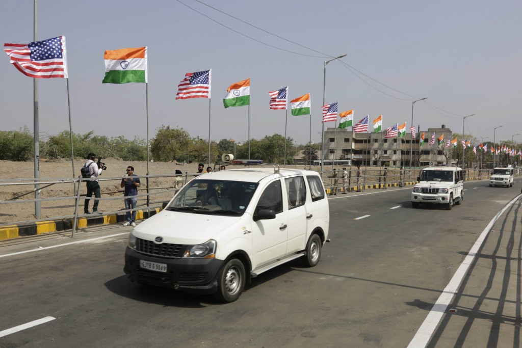 Police vehicles moves past U.S. and Indian flags erected near Sardar Patel stadium ahead of the visit of President Donald Trump in Ahmedabad, India, S...