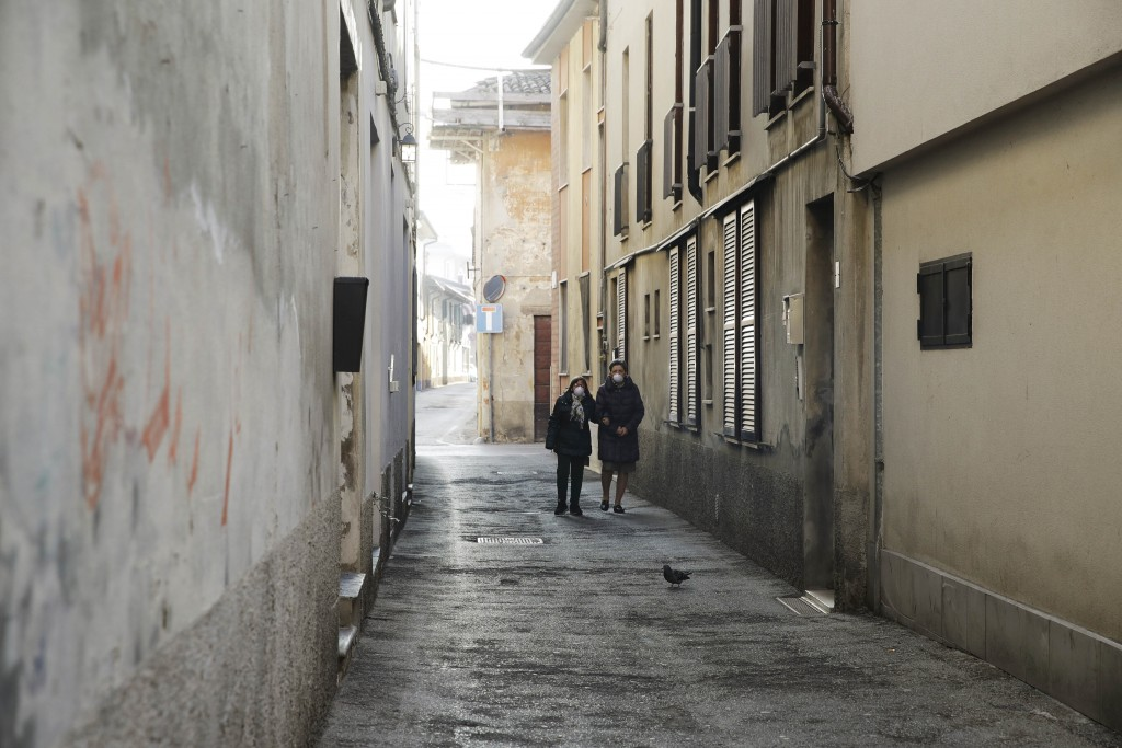 Two women wear masks as they walk in a street in Codogno, near Lodi, Northern Italy, Saturday, Feb. 22, 2020. A dozen towns in northern Italy are on e...