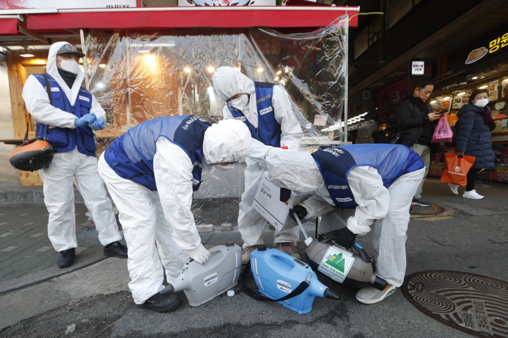 Workers wearing protective gears prepare to spray disinfectant as a precaution against the coronavirus at a market in Seoul, South Korea, Monday, Feb....