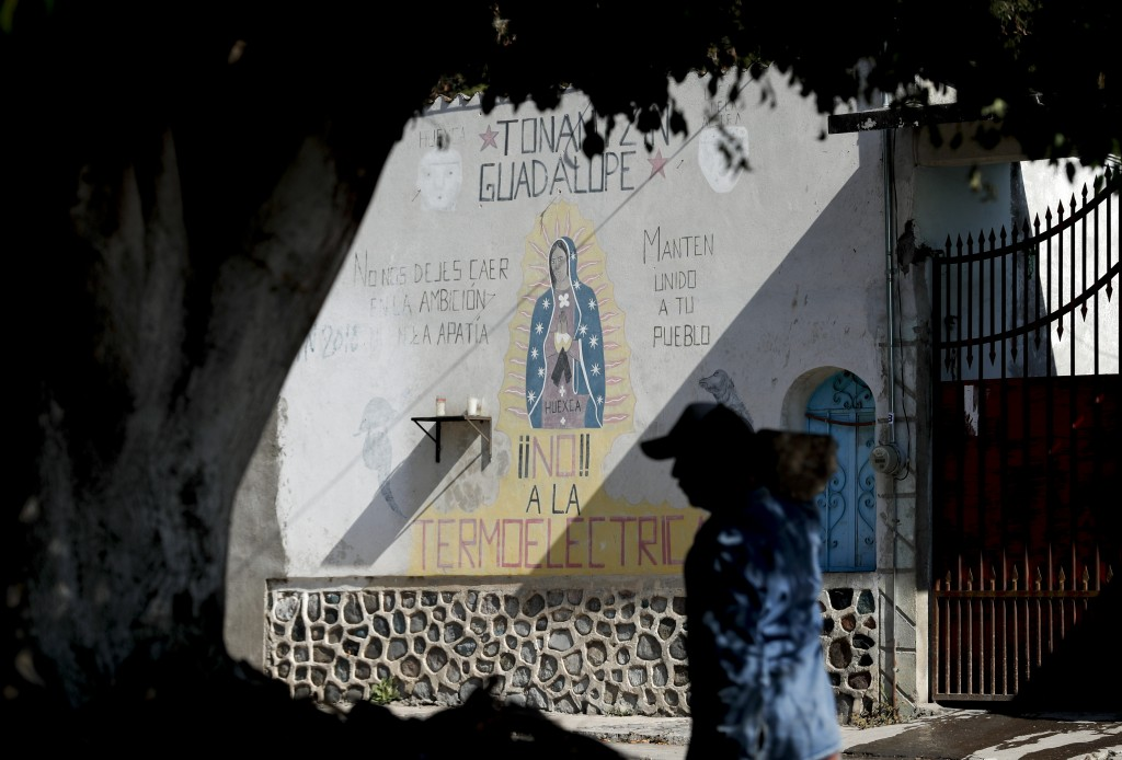 """A man walks past an image of the Virgin of Guadalupe mural with text that reads in Spanish """"No to the Thermo electric"""" in Huexca, Morelos state, Mexic..."""