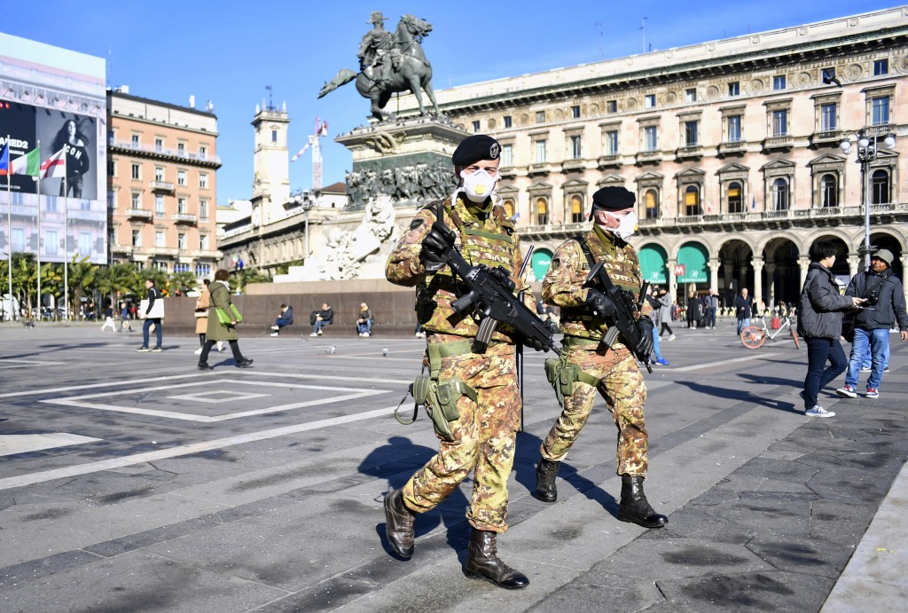 Italian soldiers wearing sanitary masks patrol Duomo square, in downtown Milan, Italy, Monday, Feb. 24, 2020. At least 190 people in Italy's north hav...