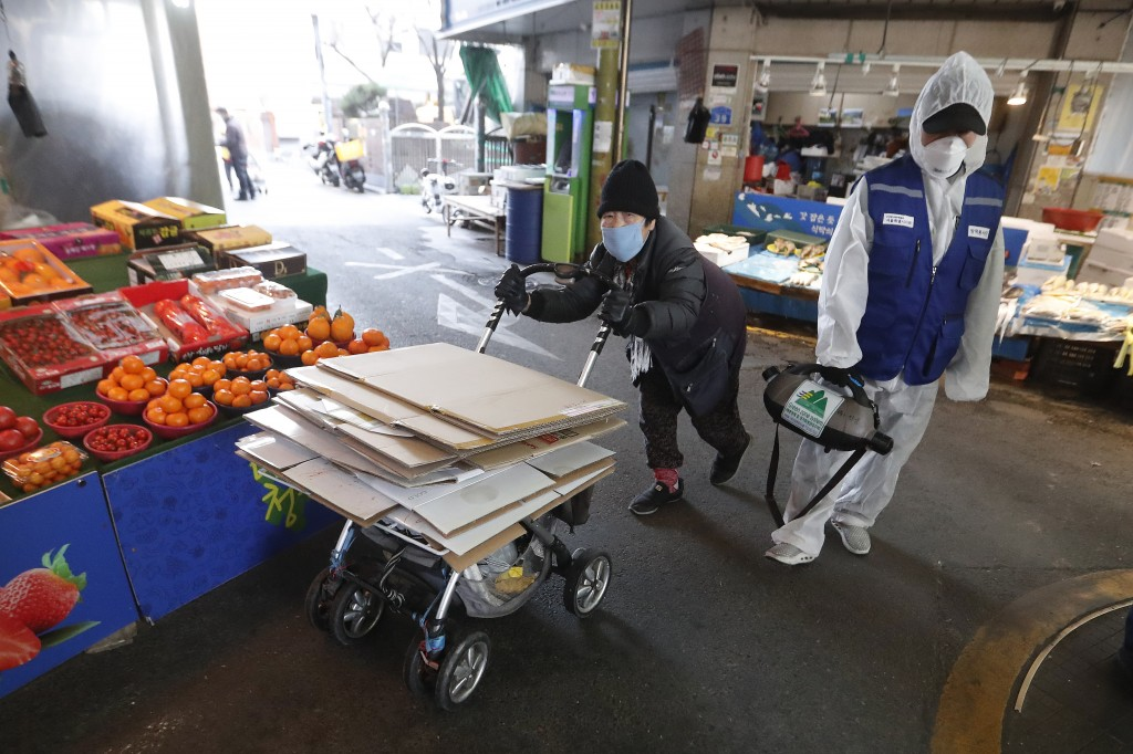 A workers wearing protective gears sprays disinfectant as a precaution against the coronavirus at a market in Seoul, South Korea, Monday, Feb. 24, 202...