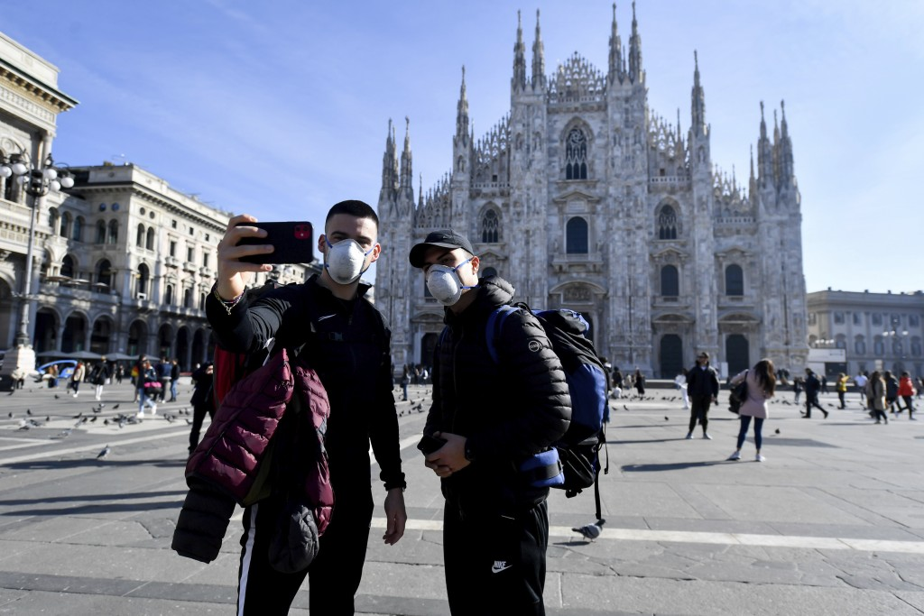 People wearing sanitary masks take a selfie in front of the Duomo gothic cathedral, in Milan, Italy, Monday, Feb. 24, 2020. At least 190 people in Ita...