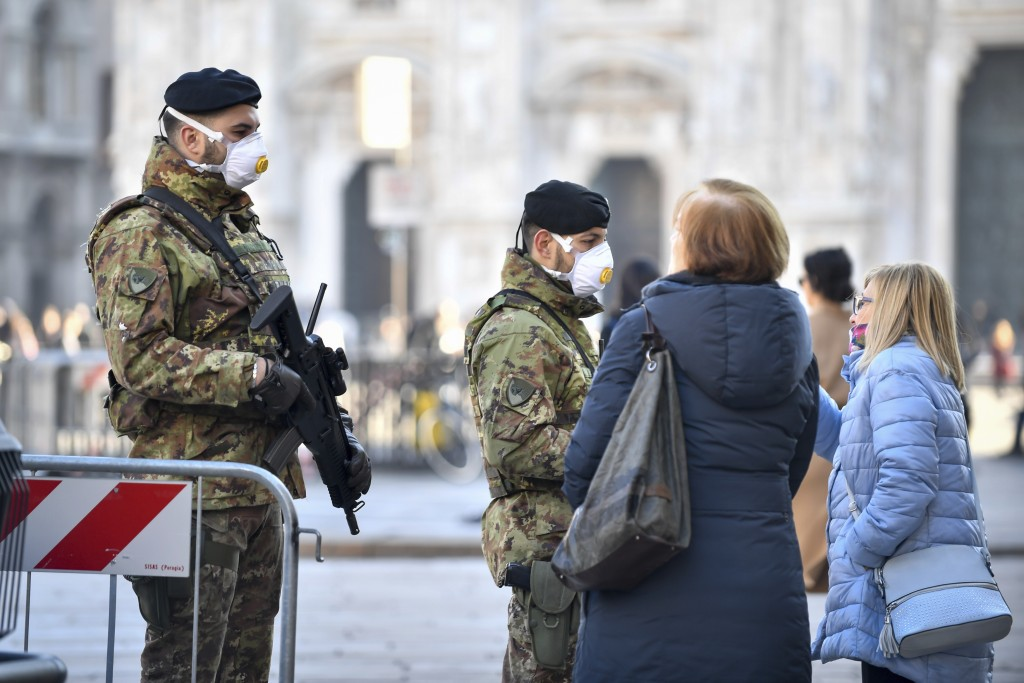 Italian soldiers wearing sanitary masks patrol Duomo square in downtown Milan, Italy, Monday, Feb. 24, 2020. At least 190 people in Italy's north have...