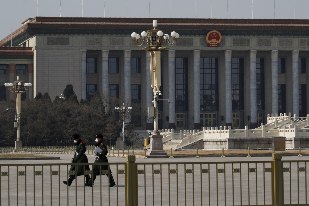 In this Sunday, Feb. 23, 2020, photo, paramilitary policemen wearing protective face masks walk by the empty Tiananmen Square against the back drop of...