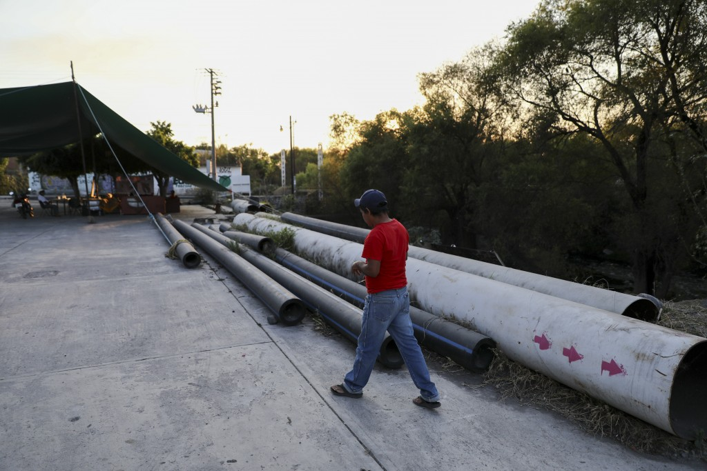 A man walks by pipes left on the ground after activists blocked the final meters construction of the thermo-electric plant pipeline in San Pedro Apatl...
