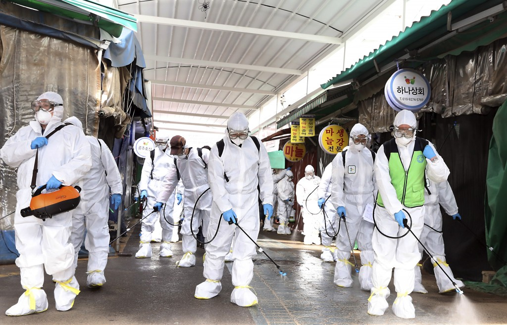 Workers wearing protective suits spray disinfectant as a precaution against the coronavirus at a market in Bupyeong, South Korea, Monday, Feb. 24, 202...