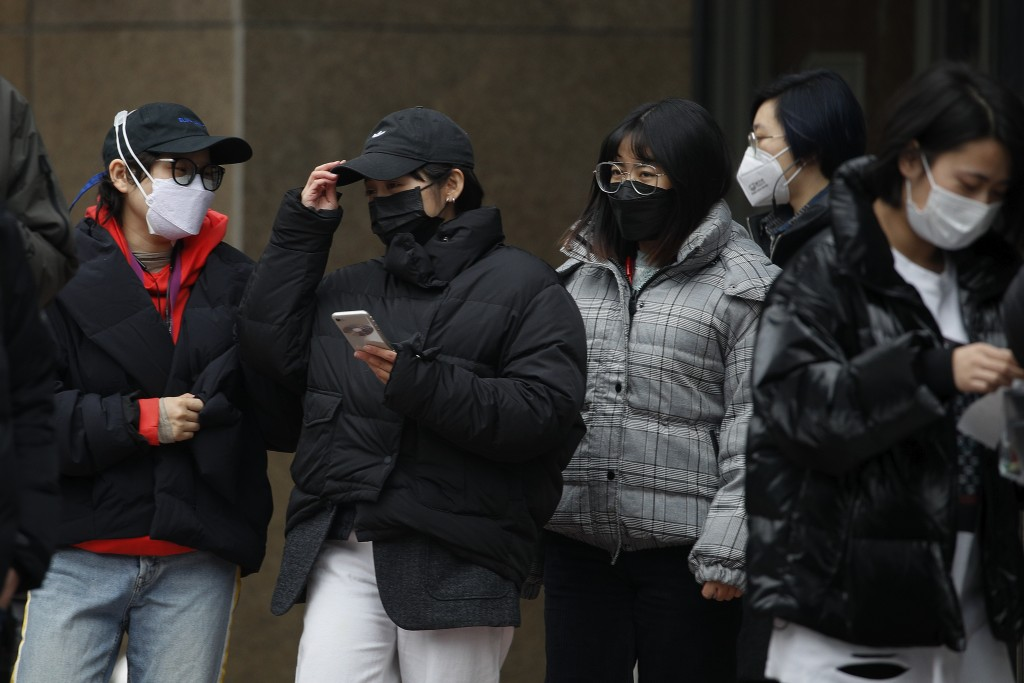 Office workers wearing protective face masks take their lunch break in Beijing, Monday, Feb. 24, 2020. China says it is postponing its most important ...