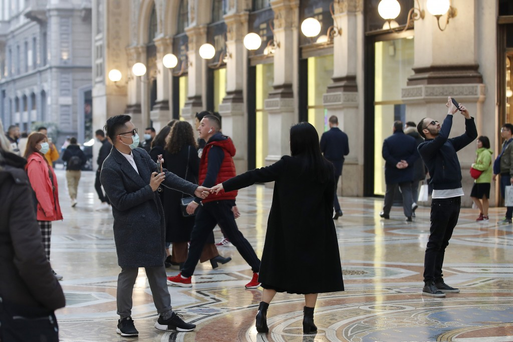 Tourists wearing sanitary masks move a few steps of dance, in downtown Milan, Italy, Sunday, Feb. 23, 2020. In Lombardy, the hardest-hit region with 9...