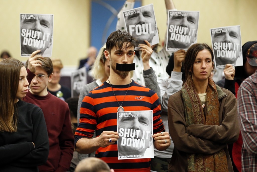 FILE - In this Jan. 8, 2019, file photo, protesters hold signs as they turn their backs on a meeting of the Virginia State Air Quality Control Board i...