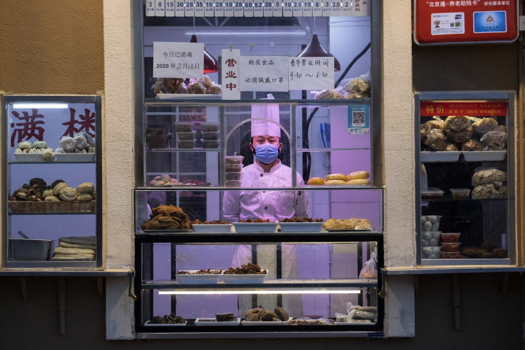 A chef looks out from behind a display of food products at a restaurant in Beijing Saturday, Feb. 22, 2020. Regulators on Monday promised tax cuts and...