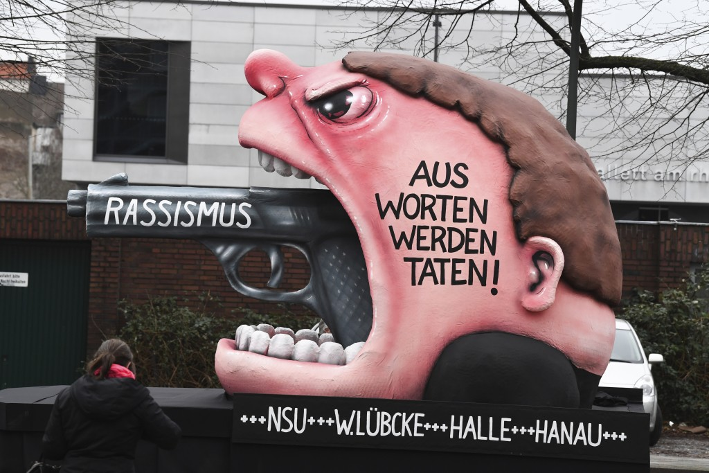 "A carnival float depicts a red-faced man yelling in rage, a pistol protruding from his mouth with the word ""racism"" on the barrel, the slogan ""from wo..."