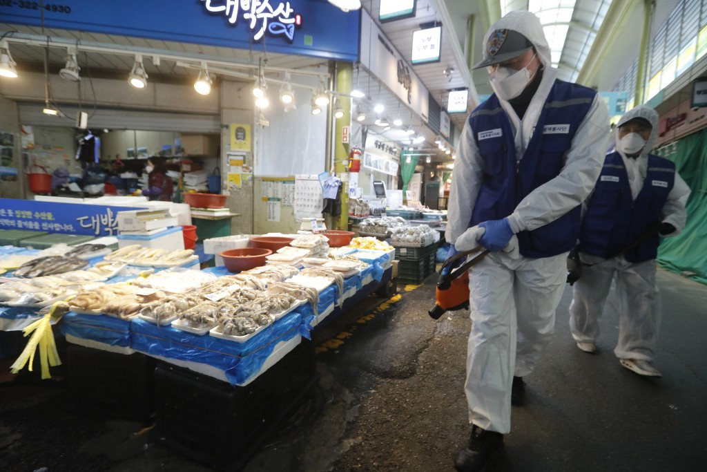 Workers wearing protective gears spray disinfectant as a precaution against the coronavirus at a market in Seoul, South Korea, Monday, Feb. 24, 2020. ...
