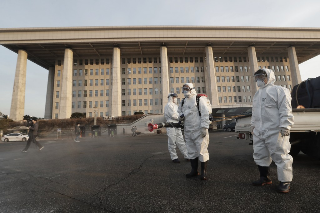 Workers wearing protective suits spray disinfectant as a precaution against the coronavirus at the National Assembly in Seoul, South Korea, Monday, Fe...