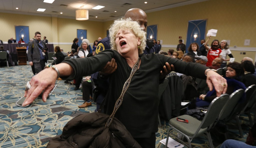 FILE - In this Jan. 8, 2019, file photo, a protester gets escorted out of a meeting of the Virginia State Air Quality Control Board by State Police in...