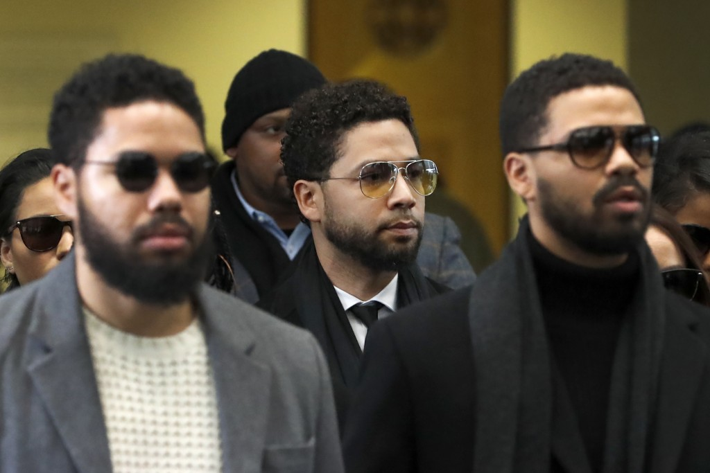 Actor Jussie Smollett, center, departs after an initial court appearance at the Leighton Criminal Courthouse, Monday, Feb. 24, 2020, in Chicago on a n...