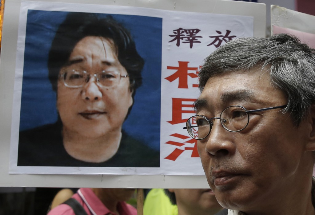 FILE - In this June 18, 2016, file photo, a picture of missing bookseller Gui Minhai is shown on a placard beside freed Hong Kong bookseller Lam Wing-...