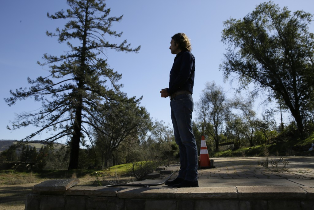 In this Tuesday, Feb. 25, 2020, photo, Jason Meek, whose Northern California wine country home was destroyed in 2017, stands in the driveway and looks...