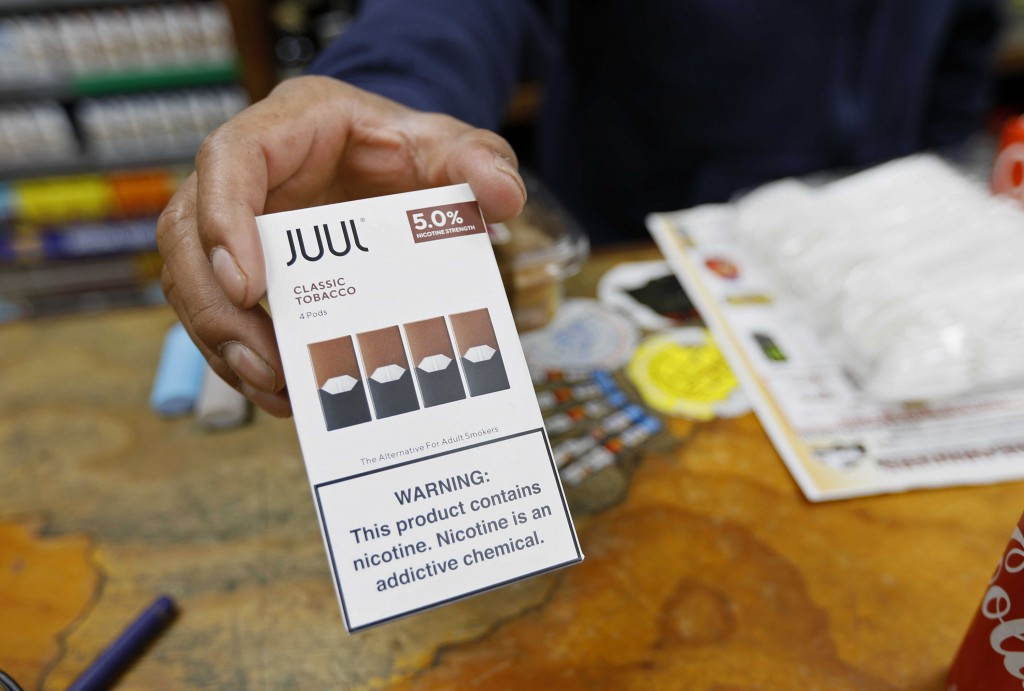 File - In this June 17, 2019, file photo, a cashier displays a packet of tobacco-flavored Juul pods at a store in San Francisco. Investigators from 39...