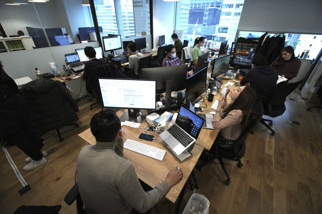 Staff of an artificial intelligence company GumGum Japan, work at their office Tuesday, Feb. 25, 2020, in Tokyo. Japanese Prime Minister Shinzo Abe sa...