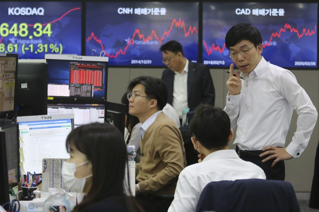 Currency traders work at the foreign exchange dealing room of the KEB Hana Bank headquarters in Seoul, South Korea, Wednesday, Feb. 26, 2020. Asian sh...