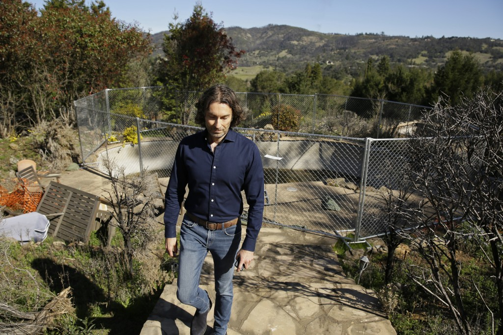 In this Tuesday, Feb. 25, 2020, photo, Jason Meek, whose Northern California wine country home was destroyed in 2017, walks through the remains of his...