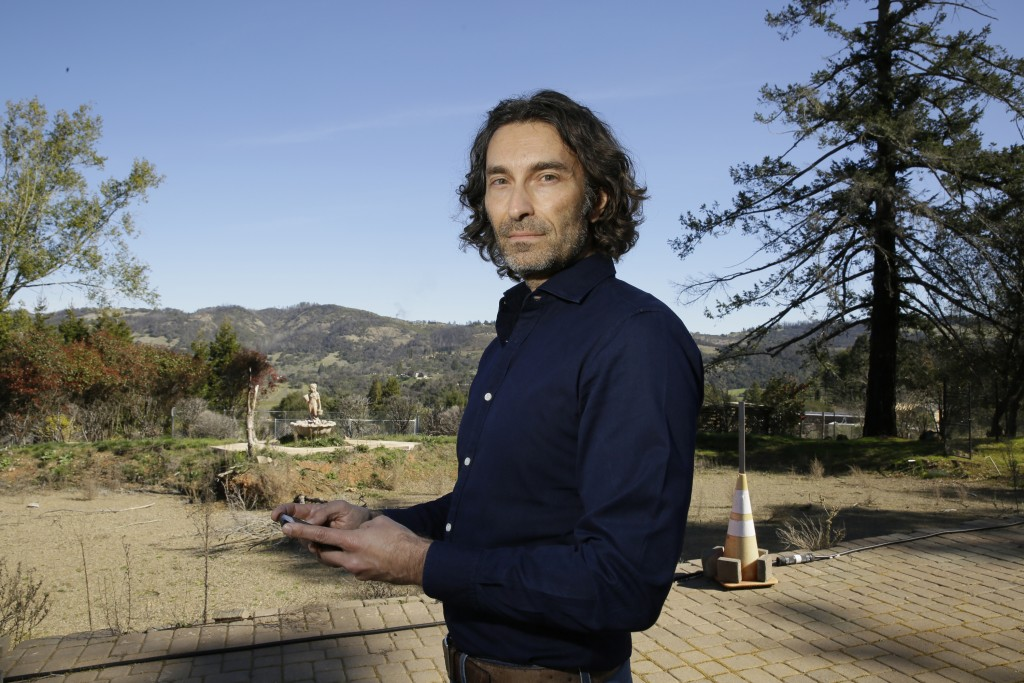 In this Tuesday, Feb. 25, 2020, photo, Jason Meek, whose Northern California wine country home was destroyed in 2017, poses for a photo as he stands i...