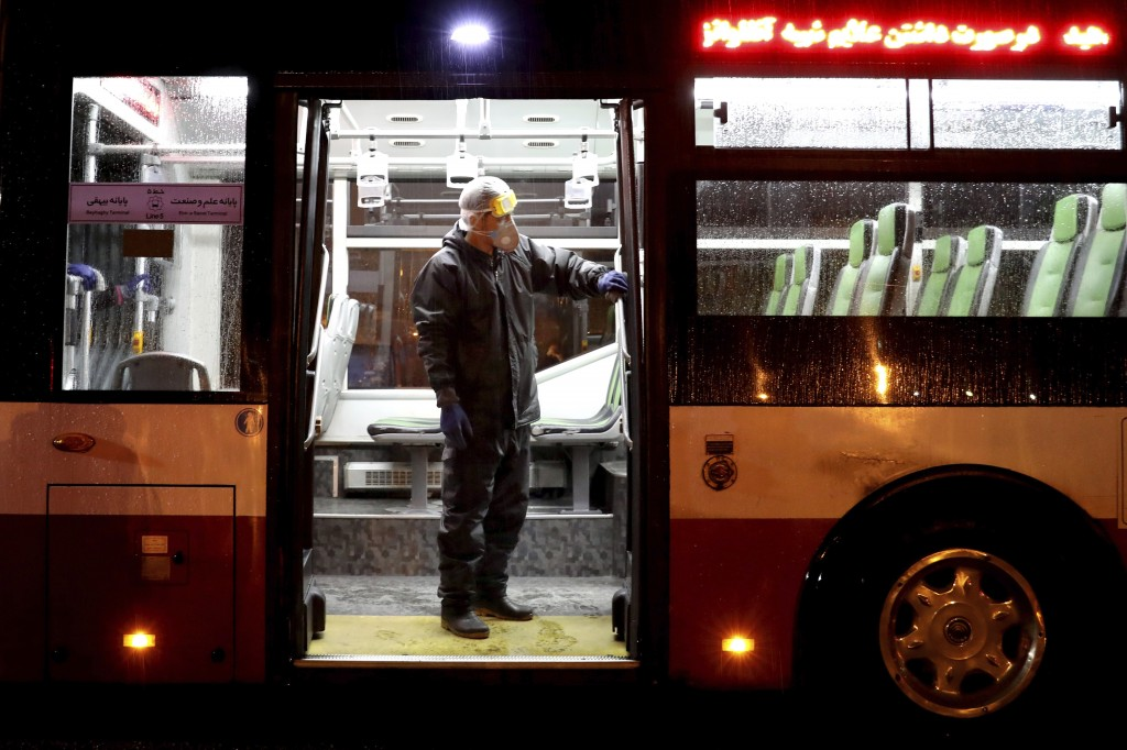 A worker disinfects a public bus against coronavirus in Tehran, Iran, in early morning of Wednesday, Feb. 26, 2020. Iran's government said Tuesday tha...