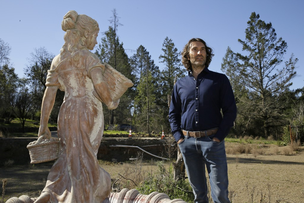 In this Tuesday, Feb. 25, 2020, photo, Jason Meek, whose Northern California wine country home was destroyed in 2017, stands by a fountain in the back...