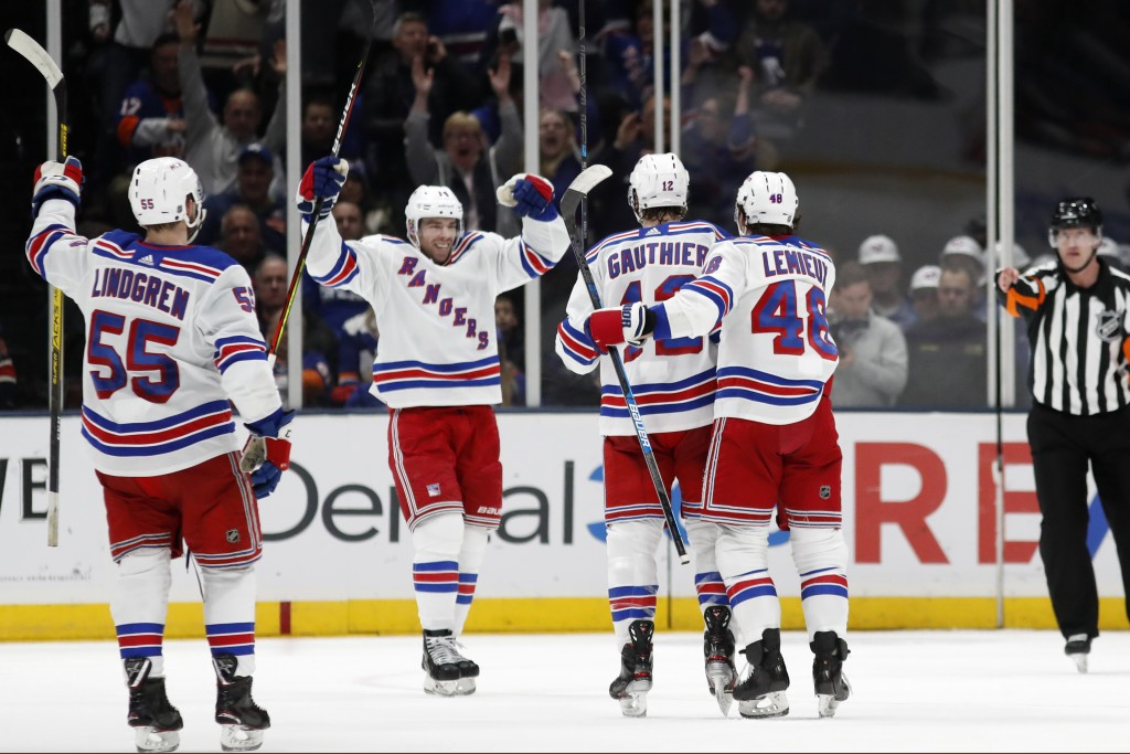 New York Rangers center Greg McKegg, second from left, celebrates with teammates after scoring a goal during the second period of an NHL hockey game a...