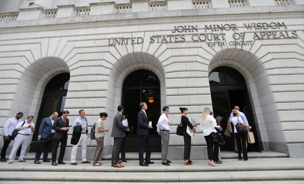 FILE - In this  July 9, 2019 file photo, people wait in line to enter the 5th Circuit Court of Appeals in New Orleans. On Wednesday, Feb. 26, 2020, th...