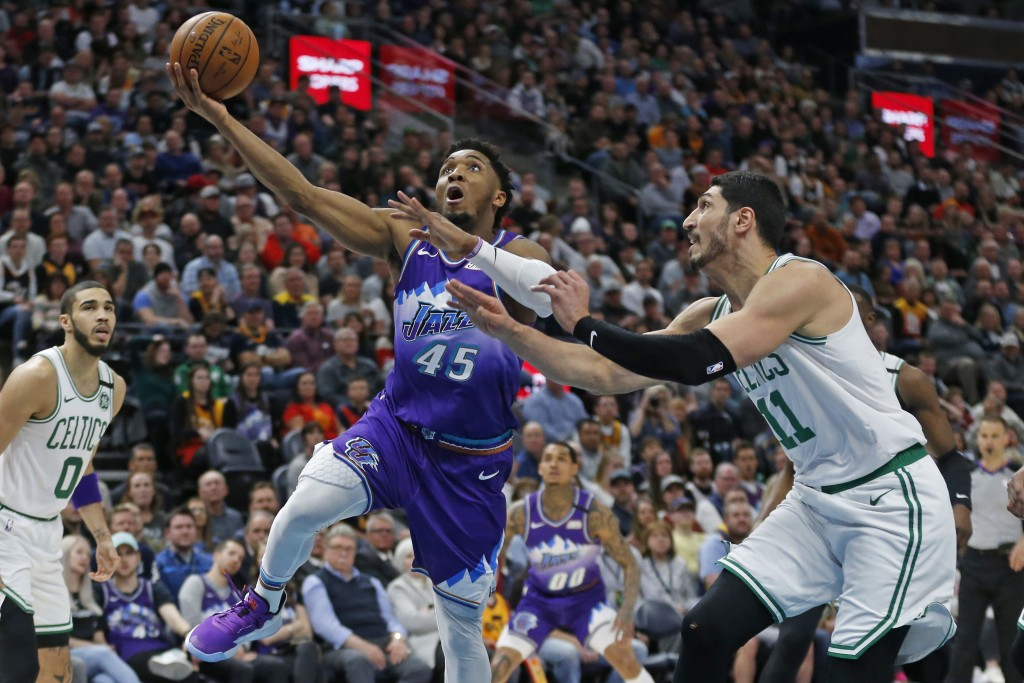 Utah Jazz guard Donovan Mitchell (45) goes to the basket as Boston Celtics center Enes Kanter (11) defends during the first half of an NBA basketball ...