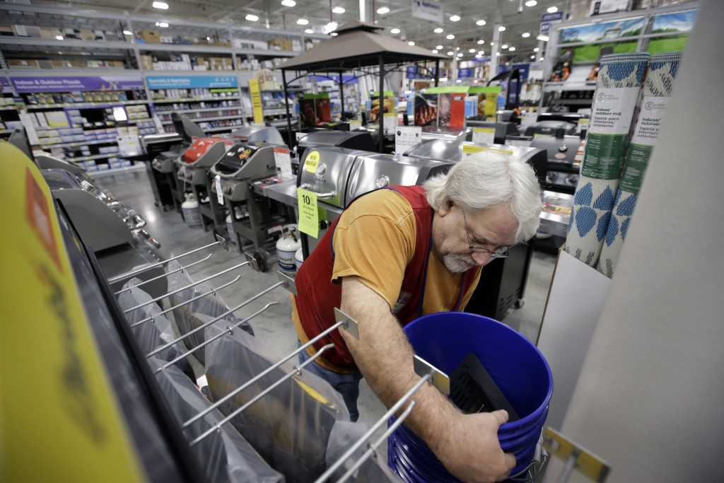 FILE- In this Feb. 23, 2018, file photo sales associate Bob Henriques, of Framingham, Mass., moves items at a Lowe's retail home improvement and appli...