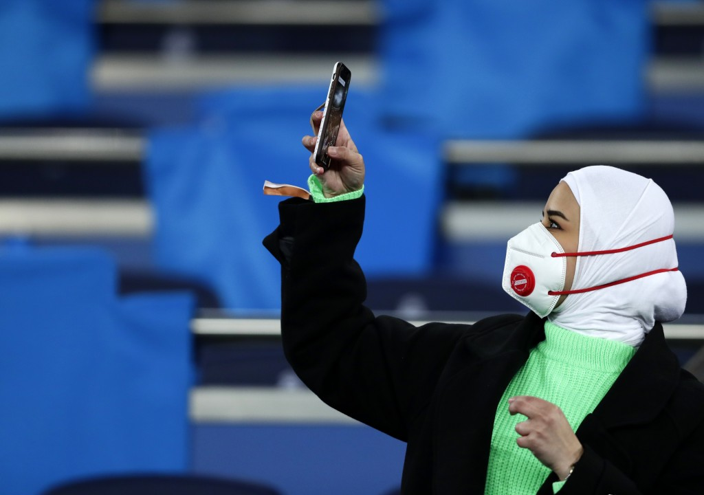 A fan wearing a protective mask takes a picture with her cell phone prior the Champions League, round of 16, first leg soccer match between Real Madri...