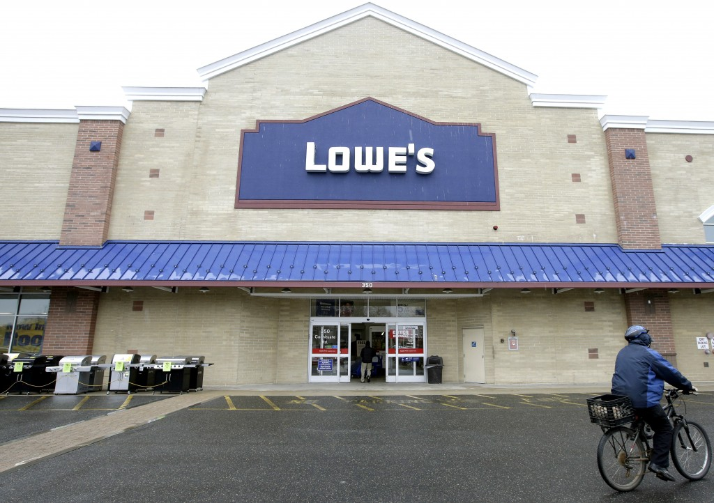 FILE - In this Feb. 23, 2018, file photo a cyclist rides near an entrance to a Lowe's retail home improvement and appliance store, in Framingham, Mass...